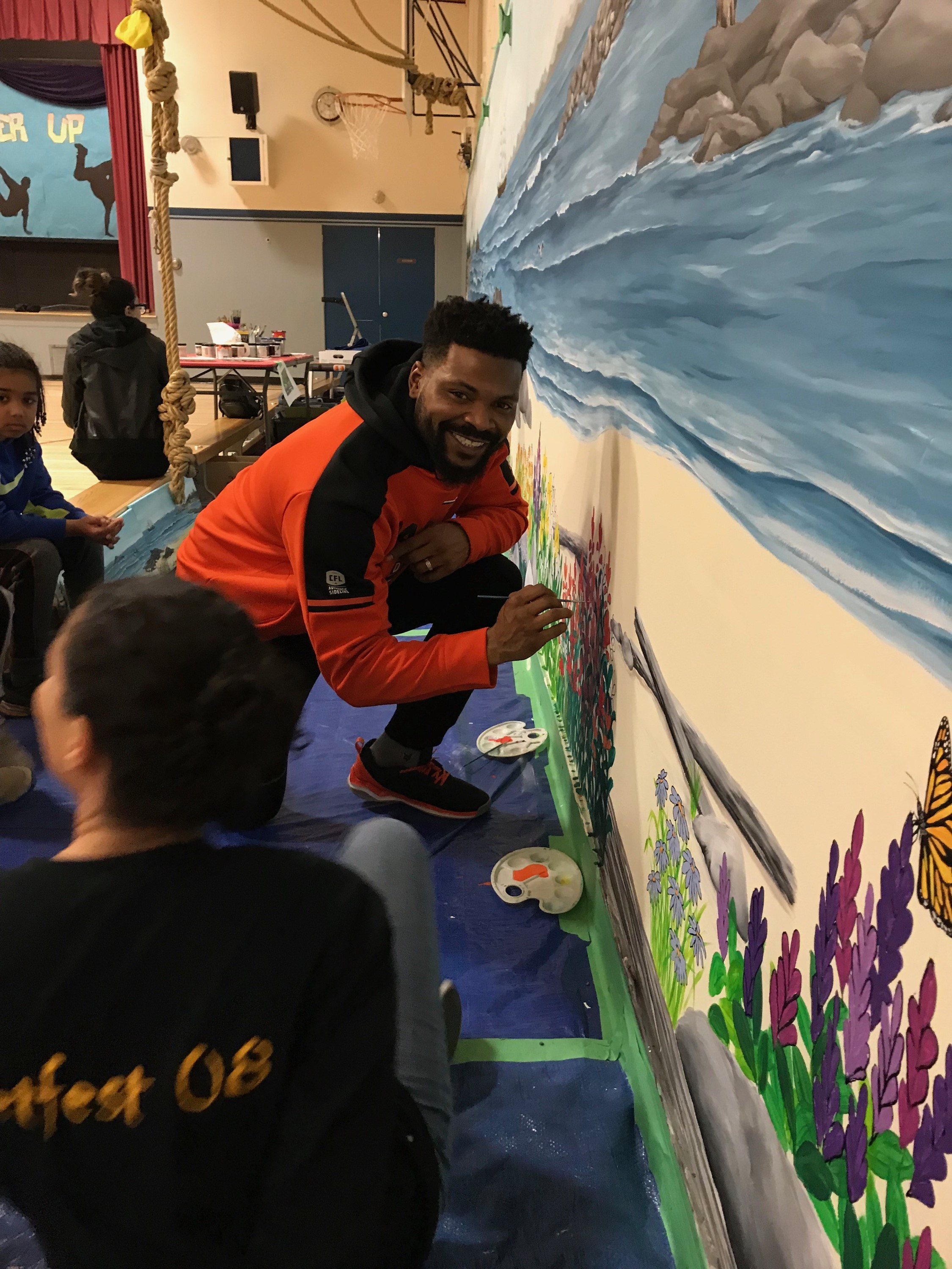 Special guest from the BC Lions adds his contribution to Cape Horn's mural!
