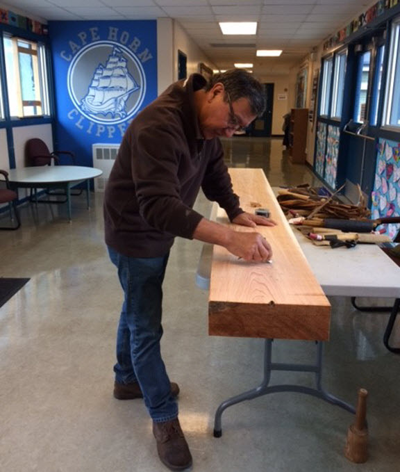 Indigenous Artist, Peter Wayne Gong at work on the outdoor classroom archway carving